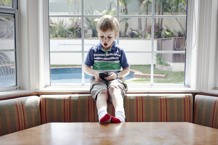 legs wide open: Boy playing handheld video game