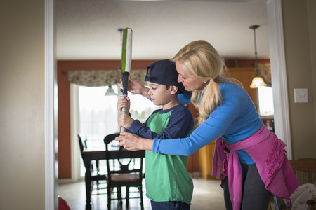 45 50: Mother teaching son to hold a baseball bat