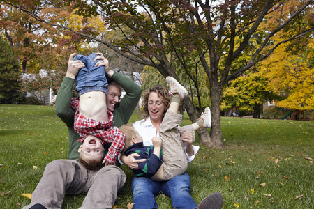 jesting: Mid adult parents and young sons playing in garden LANG_EVOIMAGES