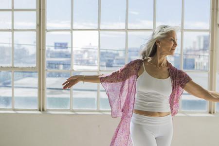 65 69 years: Graceful senior woman dancing in sunlit apartment