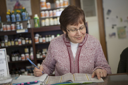 clothing store: Health foods store owner doing paperwork