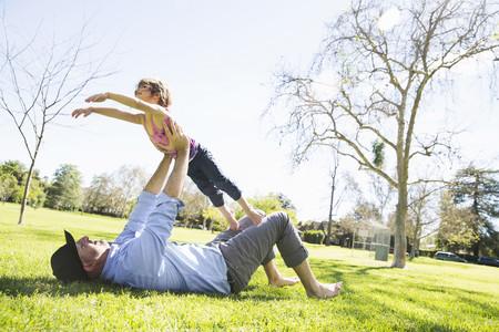 pantalones abajo: Hombre adulto medio jugando con hija en el parque