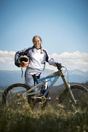 Portrait of female mountain biker holding helmet LANG_EVOIMAGES