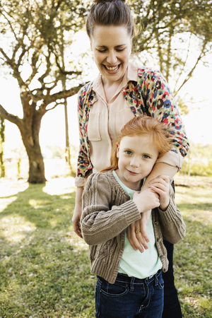 Portrait of mid adult mother with arm around daughter in park LANG_EVOIMAGES