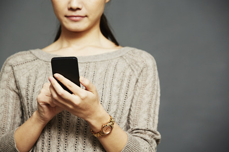 organised: Young woman using smartphone LANG_EVOIMAGES