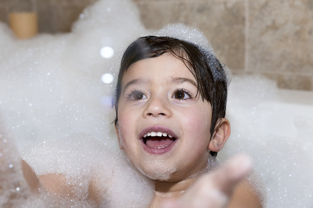 Young boy trying to catch bubble in bubble bath