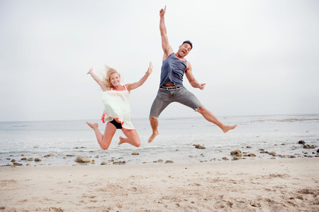 Pregnant couple jumping mid air on the beach
