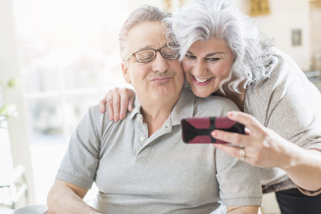 54: Affectionate mature adult couple taking a self portrait at home