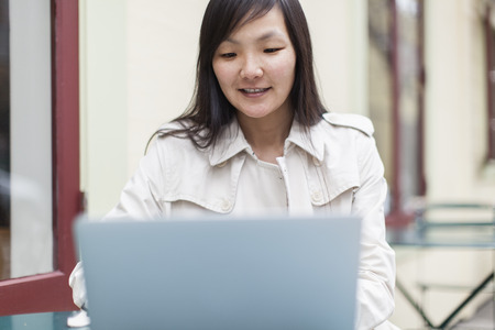 Mid adult woman using laptop outdoors