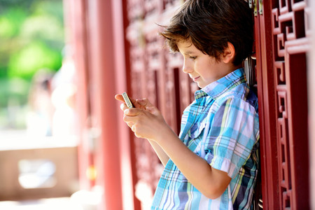 Boy leaning against red door texting on cellphone