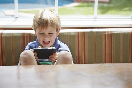 niños jugando videojuegos: Muchacho que juega el juego video handheld