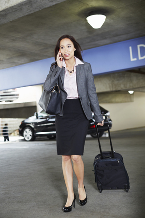 Young female businesswoman with wheeled suitcase in car park LANG_EVOIMAGES