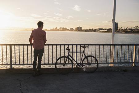 chillout: Young man gazing from pier, Long Beach, California, USA