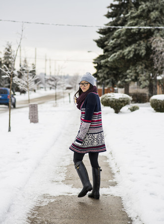 Young woman walking down snow covered street LANG_EVOIMAGES
