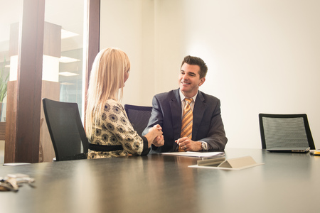 solicitors: Male and female business lawyers shaking hands in office LANG_EVOIMAGES
