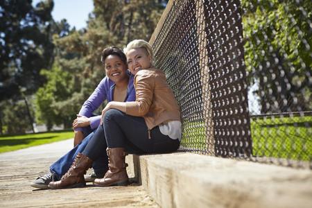 Portrait of lesbian couple sitting on park footbridge