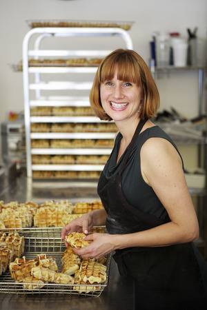 worktops: Female baker checking waffles into cooling tray