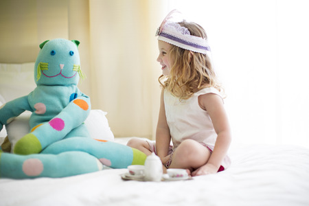 Young girl sharing tea with cuddly toy on bed
