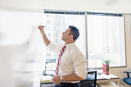 solicitors: Business lawyer writing on whiteboard in office meeting