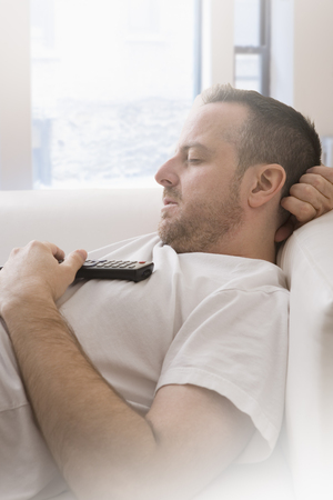 unhealthiness: Mature man with remote control asleep on sofa LANG_EVOIMAGES