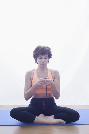 Woman meditating with prayer beads LANG_EVOIMAGES