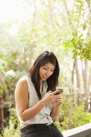 Junge Frau mit Smartphone auf Veranda