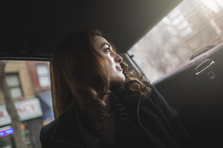 taxicabs: Young woman looking over her shoulder from taxi LANG_EVOIMAGES