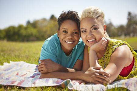 Portrait of lesbian couple lying on picnic blanket in park