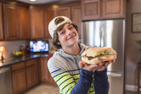 housing lot: Teenage boy in kitchen holding sandwich
