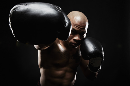punched out: Boxer with black boxing gloves punching towards camera LANG_EVOIMAGES