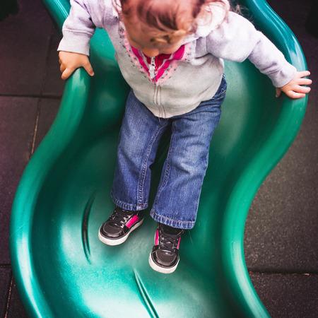 playground rides: Toddler going down slide in playground