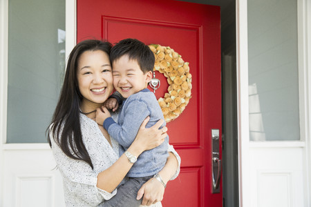 Portrait of mid adult woman and young son on porch LANG_EVOIMAGES