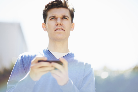 cyan business: Young man using smartphone, looking away LANG_EVOIMAGES