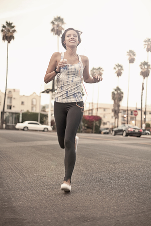 athleticism: Young athletic woman running and listening to earphones