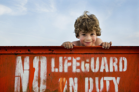 Portrait of boy and lifeguard sign, Long Beach, New York State, USA