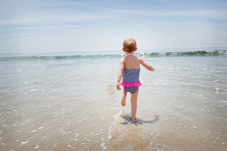 Female toddler running into the sea
