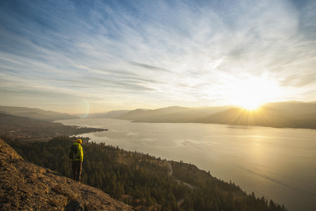 pastoral scenery: Male hiker watching sunset over Okanagan Lake, Naramata, British Columbia, Canada LANG_EVOIMAGES