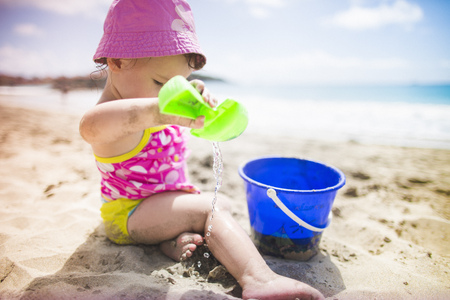 shadowed: Baby playing on sandy beach with bucket and spade
