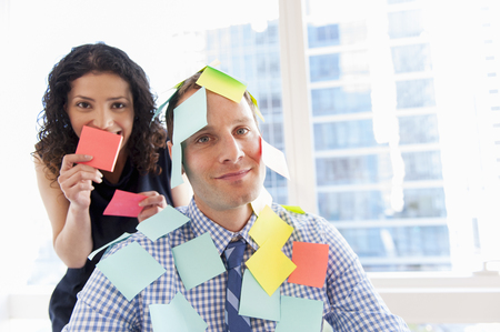 jesting: Female office worker covering male colleague with sticky notes