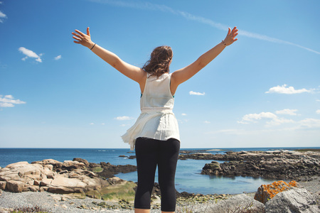 impulsive: Rear view of young woman at the rocky coastal beach in Biddeford, Maine, USA