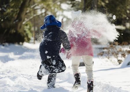 Two children running in snow
