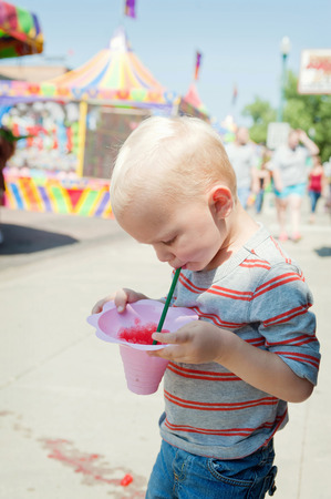 Male toddler concentrating on juice drink at funfair