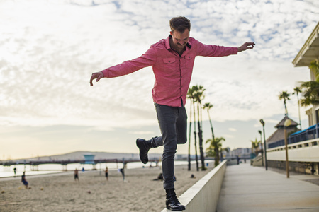 Young man balancing on wall, Long Beach, California, USA