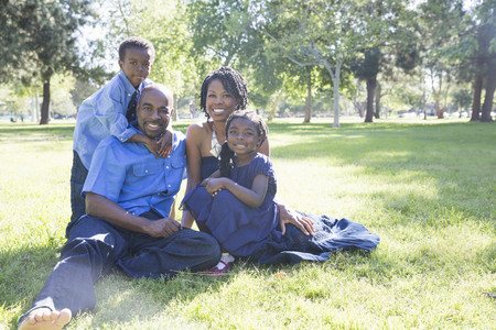 sweet grasses: Portrait of mature couple with son and daughter sitting in park LANG_EVOIMAGES