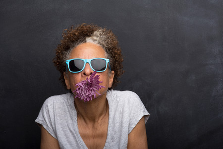 impulsive: Studio portrait of senior woman with flower in her mouth LANG_EVOIMAGES