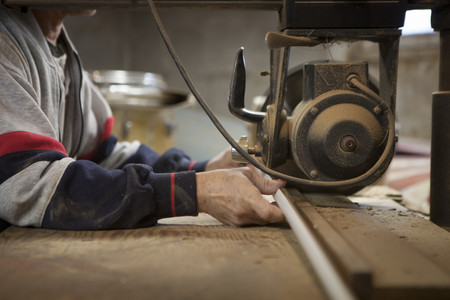 new age: Close up of man using radial arm saw in workshop