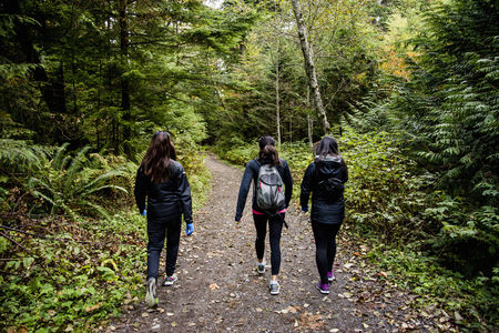anorak: Three young female hikers walking through wood, Squamish, British Columbia, Canada LANG_EVOIMAGES