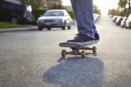 Boy skateboarding on road, close up