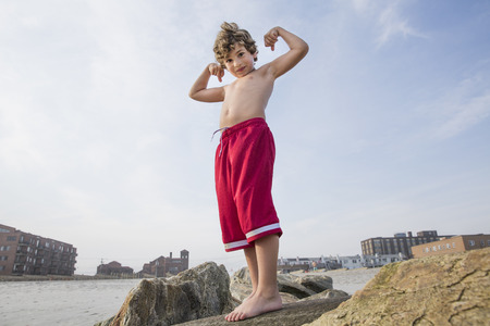 state of mood: Boy at the coast showing off his arm muscles, Long Beach, New York State, USA LANG_EVOIMAGES