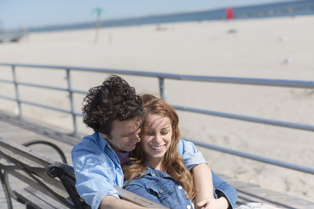 state of mood: Romantic couple on park bench at beach LANG_EVOIMAGES